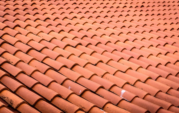 closeup view of slightly old red roof tile shingles