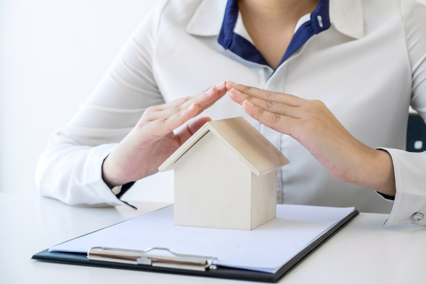 woman from insurance holding hand over miniature model house